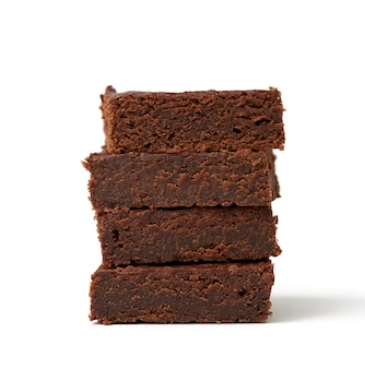 Stapel vierkant gebakken stukken van de cake van de browniechocolade die op een witte achtergrond wordt geïsoleerd