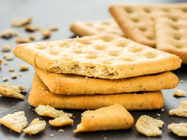 Stapel vierkante crackers met stukjes en kruimels op leigrijs