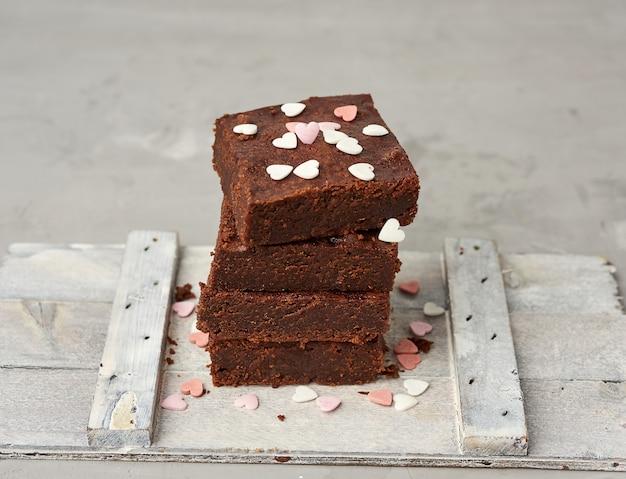 Stapel vierkante gebakken de cakeplakken van de browniechocolade op een witte achtergrond