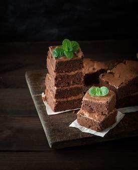 Stapel vierkante stukjes gebakken bruine brownietaart op een houten bord, bovenop is een groen muntblad