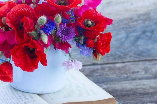 Stapel vintage oude boeken op tafel met verse veld bloemen