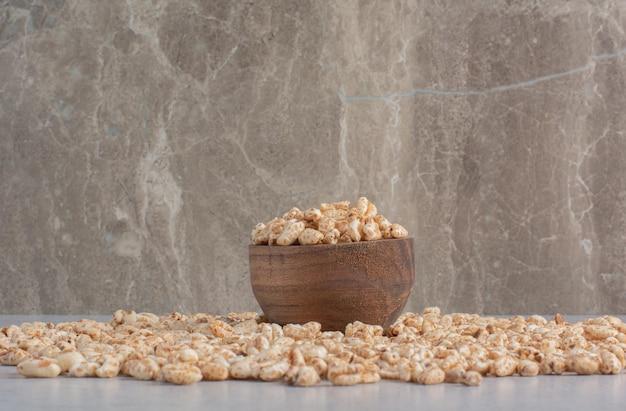 Stapel vlokken in een kom en eromheen verspreid op marmeren oppervlak