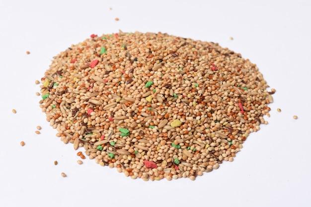 Stapel voedsel voor parkietenmengsel van granen op witte achtergrond