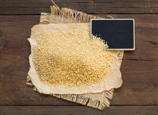 Stapel volkoren couscous met een klein bord bovenaanzicht op hout
