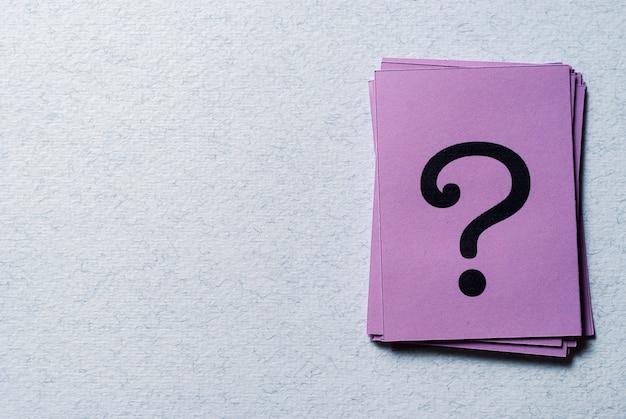 Stapel vraagtekens op paars papier