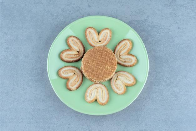 Stapel wafel en koekjes op groene plaat.