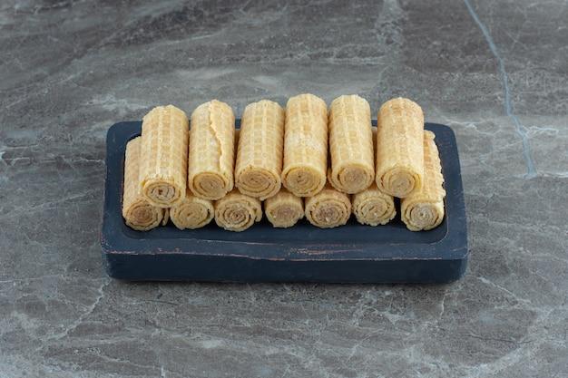 Stapel wafelbroodjes op een houten bord over grijze tafel.