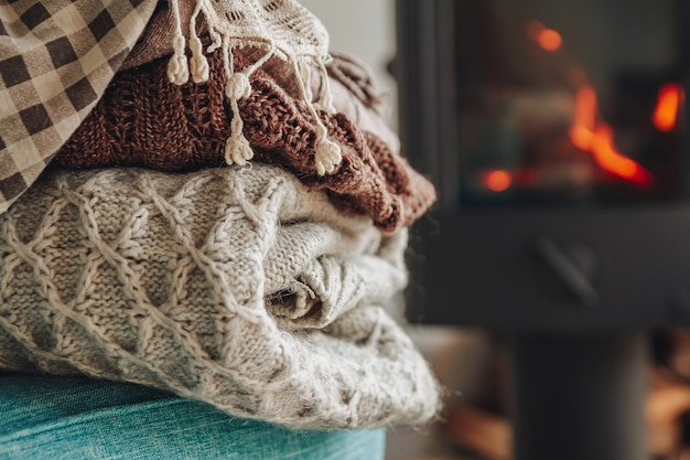 Stapel warme kleren op een fauteuil een ijzeren open haard