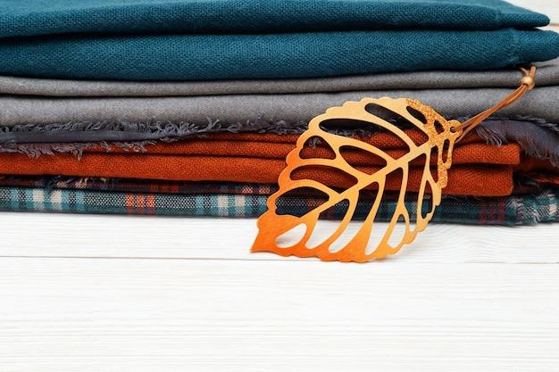 Stapel warme wollen sjaal versierd herfstbladeren.