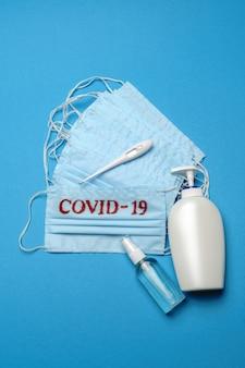 Stapel wegwerp blauwe medische gezichtsmaskers met covid-19 teken en alcohol handdesinfecterend antiseptisch middel op blauwe achtergrond
