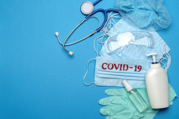 Stapel wegwerp blauwe medische gezichtsmaskers met covid-19 teken, rubberen latex handschoenen, bril, stethoscoop en alcohol handdesinfecterend antiseptisch middel op blauwe achtergrond