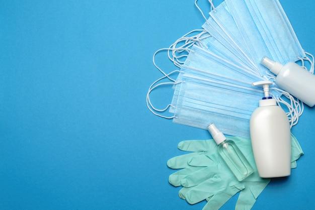 Stapel wegwerp blauwe medische gezichtsmaskers, rubberen latex handschoenen en alcohol handdesinfecterend antiseptisch middel op blauwe achtergrond