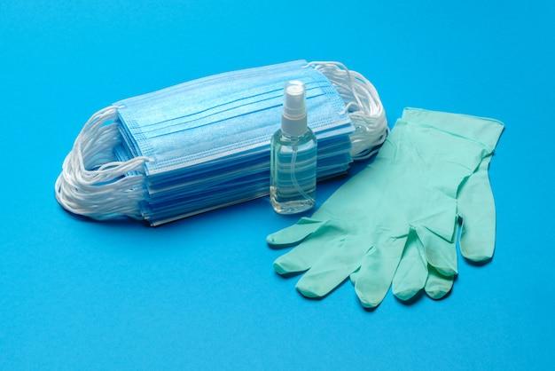 Stapel wegwerp blauwe medische gezichtsmaskers, rubberen latex handschoenen en alcohol handdesinfecterend middel antiseptisch op blauwe muur