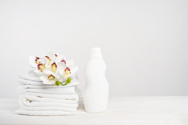 Stapel wit linnen, wasgel en wasverzachter op een witte tafel met orchideebloemen. mockup wasdag in een tropisch hotel met kopieerruimte.
