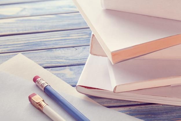Stapel witte boeken met potloden