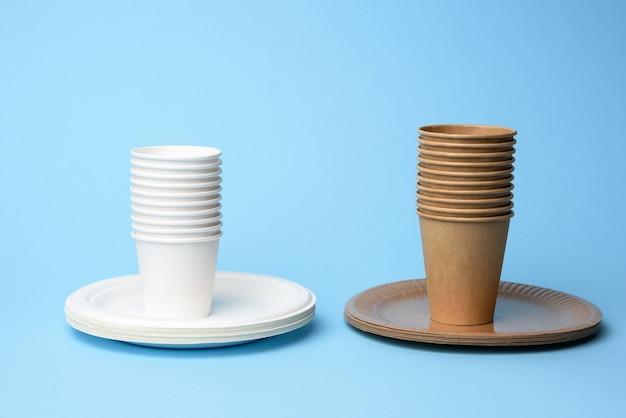 Stapel witte en bruine papieren bekers en ronde borden op een blauwe achtergrond, nul afval