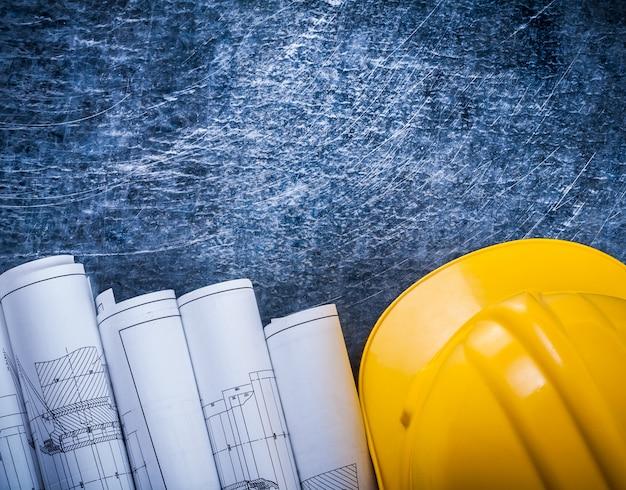 Stapel witte gerolde blauwdrukken en bouwhelm op de metaal gekraste lijstbouw en architectuurconcept