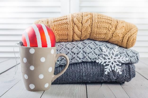 Stapel witte gezellige gebreide sweaters op een houten tafel