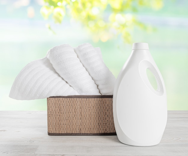 Stapel witte handdoeken in de mand en de witte lege fles wasgel.