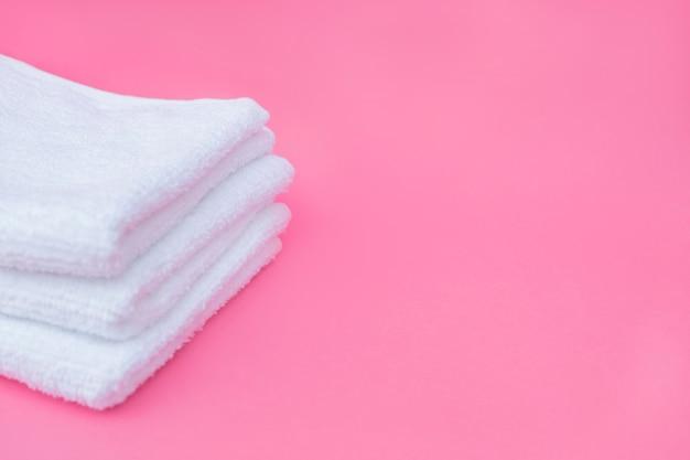 Stapel witte handdoeken op roze achtergrond