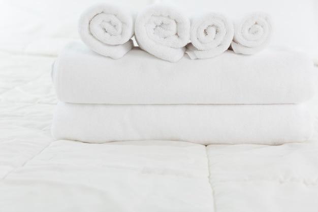 Stapel witte handdoeken op wit bed in moderne slaapkamer