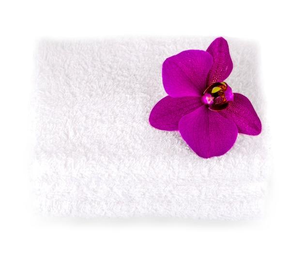 Stapel witte kuuroordhanddoeken met purpere orchideebloem.