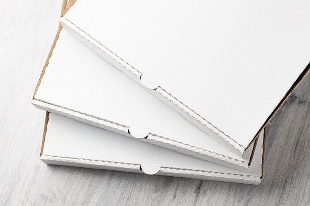 Stapel witte lege kartonnen pizzadozen op houten tafel. bovenaanzicht.