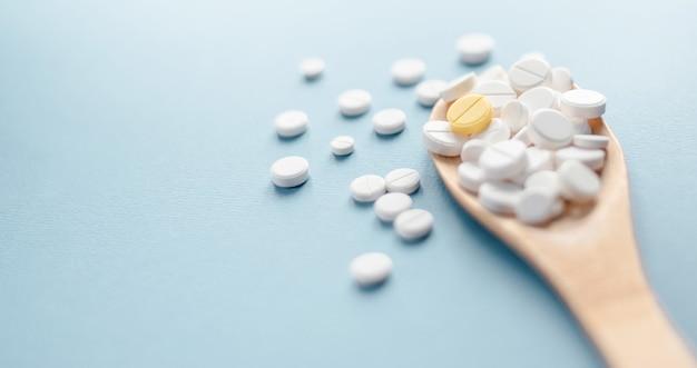 Stapel witte pillen en capsules met één gele capsule in centrum op houten lepel