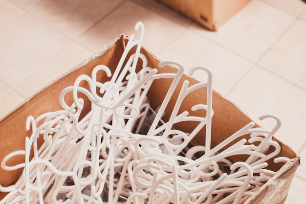 Stapel witte plastic kleerhangers in een doos close-up