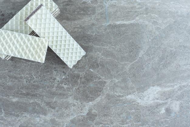Stapel witte wafeltjes op grijze achtergrond.