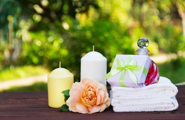 Stapel witte zachte handdoeken, geurige olie, rozen en kaarsen op onscherpe groene achtergrond.