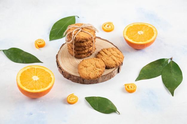 Stapel zelfgemaakt koekje op een houten bord en half gesneden sinaasappel met bladeren op een wit oppervlak.