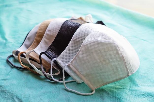 Stapel zelfgemaakte beschermende herbruikbare antivirale maskers op groene doek