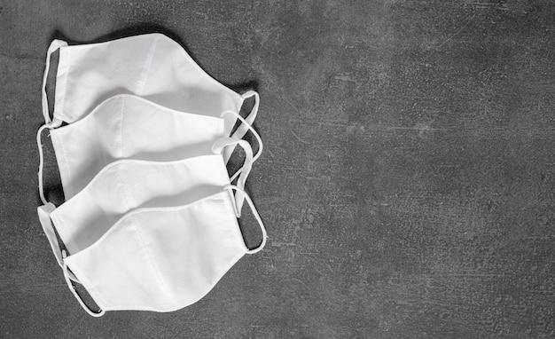 Stapel zelfgemaakte beschermende herbruikbare antivirale maskers op zwarte achtergrond