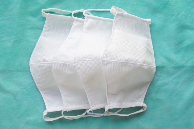 Stapel zelfgemaakte beschermende herbruikbare antivirale witte maskers op groene doek