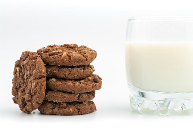 Stapel zelfgemaakte chocoladekoekjes met glas melk.
