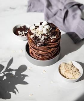 Stapel zelfgemaakte chocoladepannekoeken met gesmolten chocolade amandel en marshmallow direct zonlicht en harde schaduwen