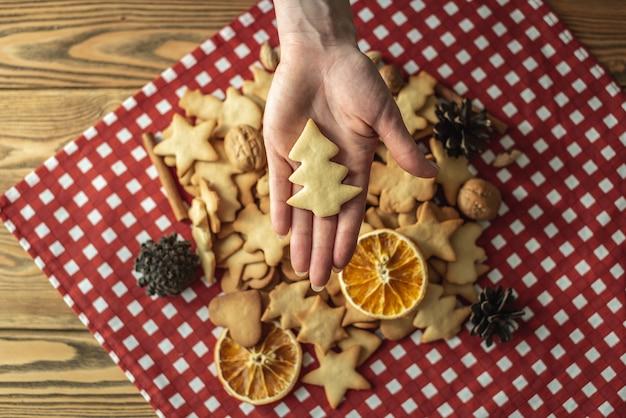 Stapel zelfgemaakte koekjes op het rode tafelkleed en de hand van een vrouw houdt een koekje in de vorm van een kerstboom vast