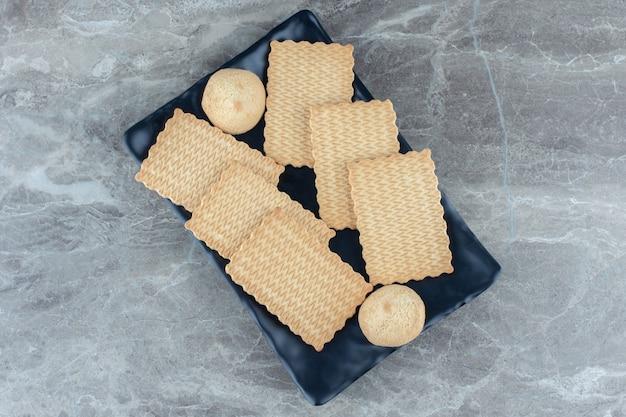 Stapel zelfgemaakte koekjes op zwarte keramische plaat.