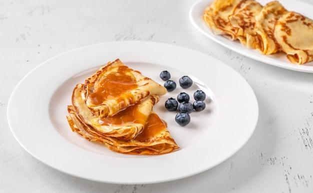 Stapel zelfgemaakte pannenkoeken gegarneerd met karamel en verse bosbessen