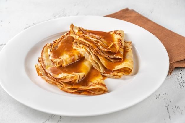 Stapel zelfgemaakte pannenkoeken gegarneerd met karamel