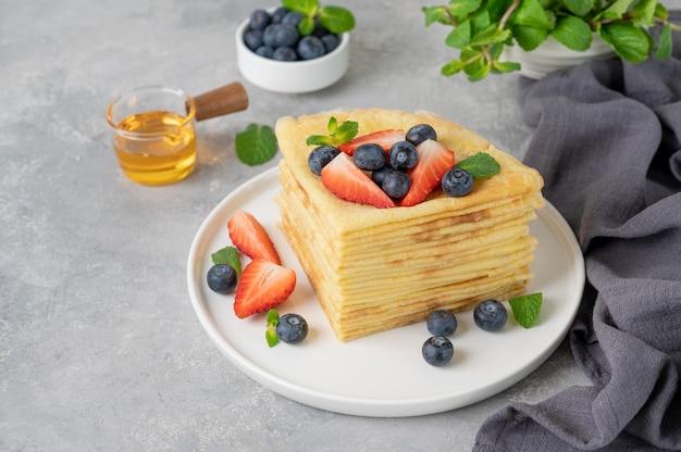 Stapel zelfgemaakte pannenkoeken geserveerd met verse bosbessen en aardbeien op een witte plaat op een grijze betonnen achtergrond. voedsel voor maslenitsa. kopieer ruimte.
