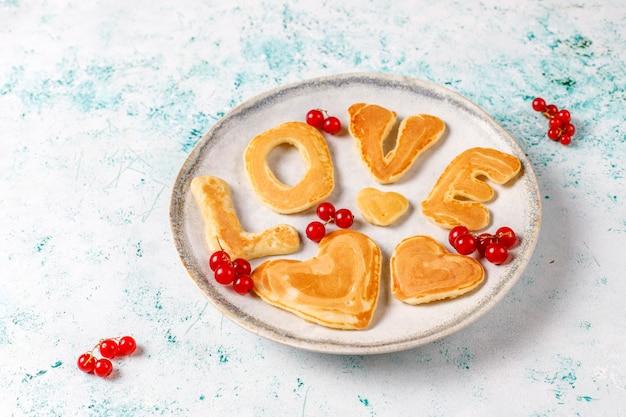 Stapel zelfgemaakte pannenkoeken met honing siroop en bessen.