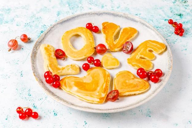 Stapel zelfgemaakte pannenkoeken met honingsstroop en bessen.