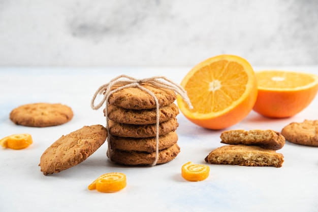 Stapel zelfgemaakte verse koekjes met biologische sinaasappelen.