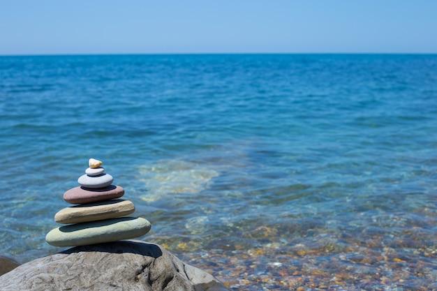 Stapel zen stenen in de buurt van zee. harmonie, balans.