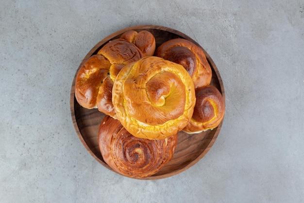 Stapel zoete broodjes, op een klein dienblad op marmeren tafel.