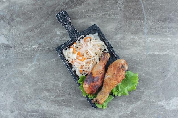 Stapel zuurkool en gegrilde kip drumsticks op houten bord over grijze tafel.