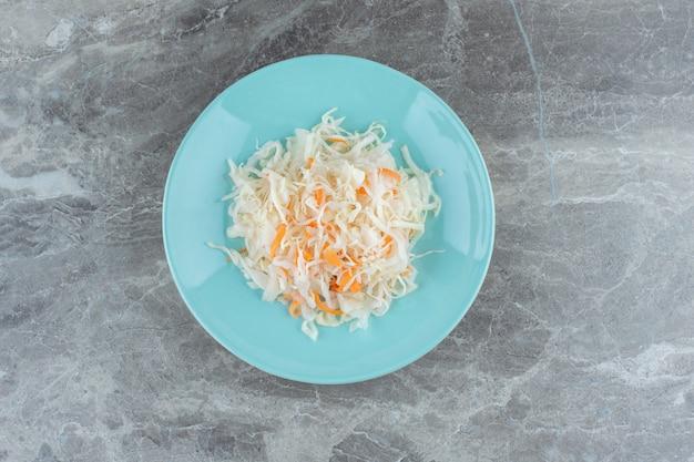 Stapel zuurkool op blauw bord over grijs.