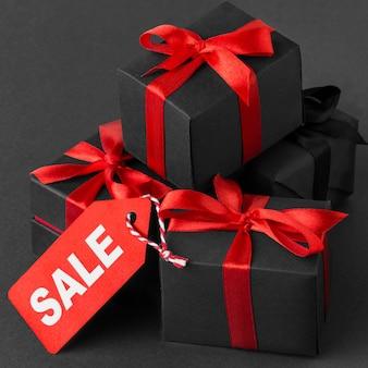 Stapel zwart ingepakte cadeaus en rood lint